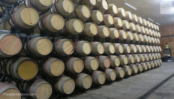 Notice the barrel on the left, second row from the bottom. The barrel has a clear plexiglass bottom so that you can see inside (just for tours—they won't really use this) and you can see how the wine settles. The wines are on special rollers to keep the sediment from settling in one spot.