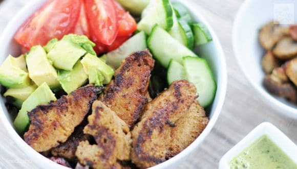 close up of bowl of vegan steak salad with seitan, avocado, tomato, and cucumber
