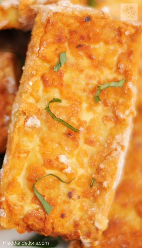 close up of crispy pizza tofu nuggets with basil garnish