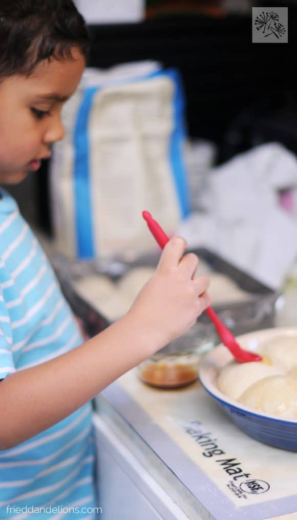 young boy making maple dinner rolls with aquafaba
