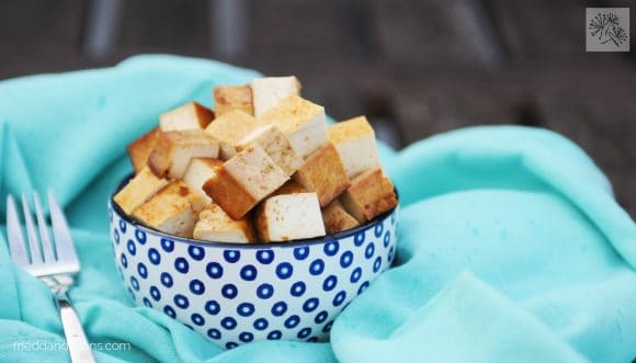 white bowl with blue polka dots filled with baked tofu