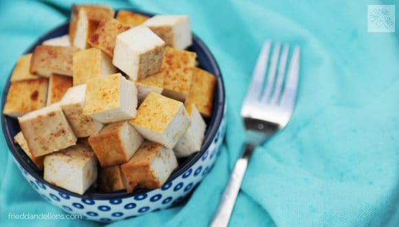 bowl of baked tofu with blue background and fork